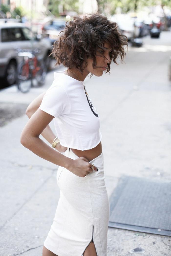 Frau im monochromen weißen Outfit, langer Rock mit Reißverschlüssen an den Seiten, kurzes weißes T-Shirt, Naturlocken Frisuren