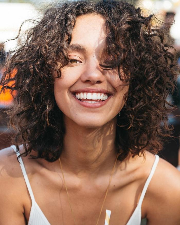 Nahaufnahme einer lächelnden Frau mit kurzen dunklen Haaren, Kurzhaarfrisuren mit Locken, weißes Top mit Spaghetti-Träger