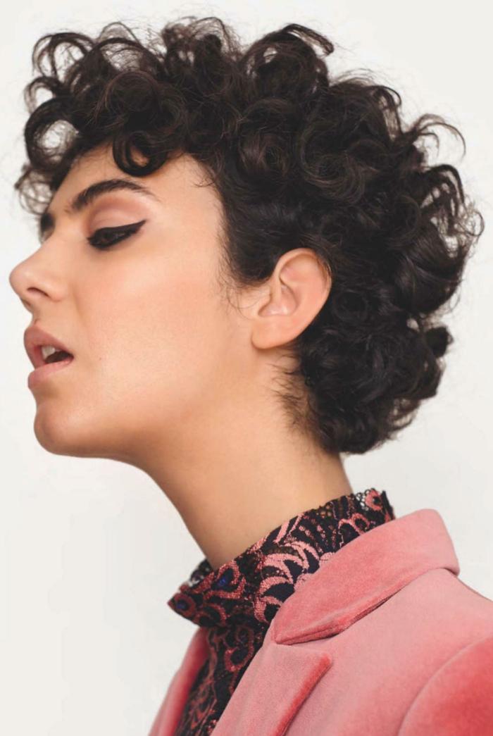 Naturlocken kurz schneiden, dunkle Haare, geschminkt mit Eyeliner, schwarz pinke Bluse und pinker Mantel