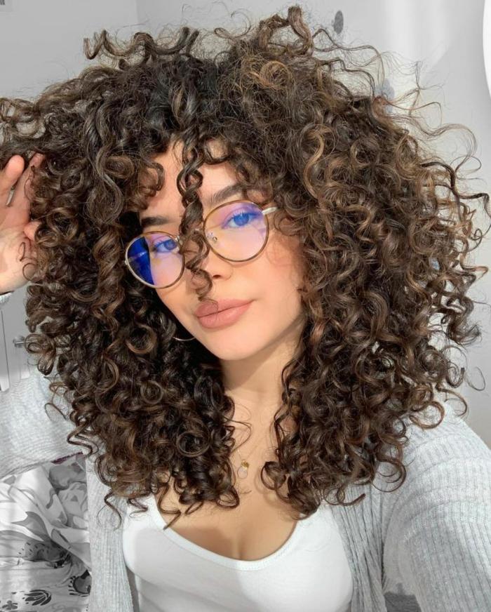 Nahaufnahme einer Frau mit lockigen braunen Haaren, große runde Brillen, Moderne Kurzhaarfrisuren, weißes Top und grauer Cardigan