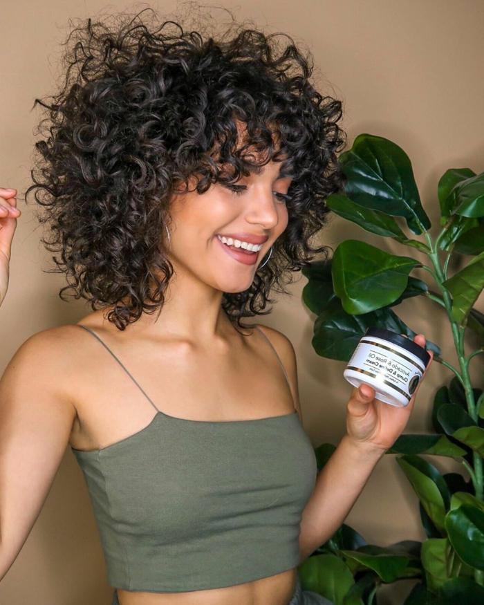 Modische Kurzhaarfrisuren für lockiges Haar, Dame im grünen Tanktop mit Spaghetti-Trägern, Pflegeprodukt für Haar in der Hand, grüne Pflanze,