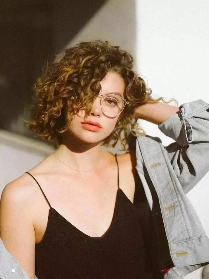 Frau im schwarzen Tanktop mit Spaghetti-Trägern und Jeansjacke, Kurzhaarfrisuren Locken, große runde Brillen