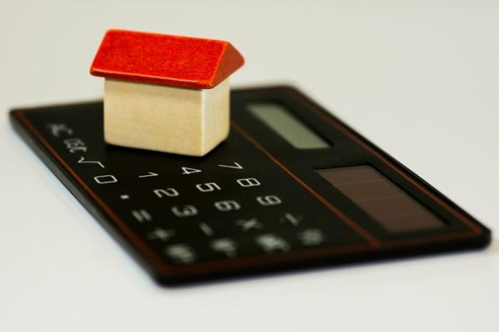Neues Haus oder neue Wohnung mit einem Umzugskredit finanzieren, schwarzer Taschenrechner, kleines Deko-Haus