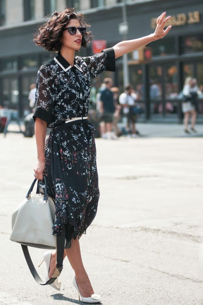 Street Style Fashion Ideen, schwarzes langes Kleid mit blauen Motiven, kurze Haare Locken, weiße Tasche und Schuhe,