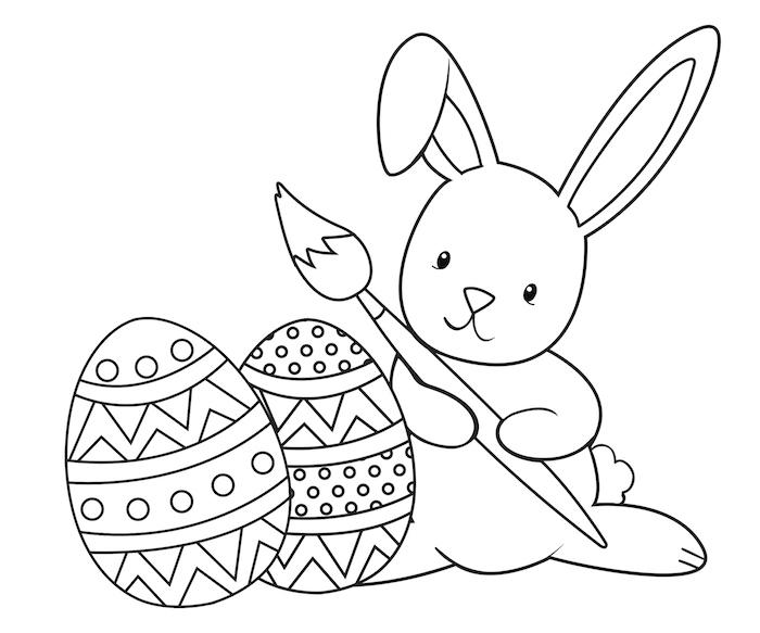 Ausmalbild Osterhase, Hase mit Pinsel und zwei Ostereier mit Dekorationen