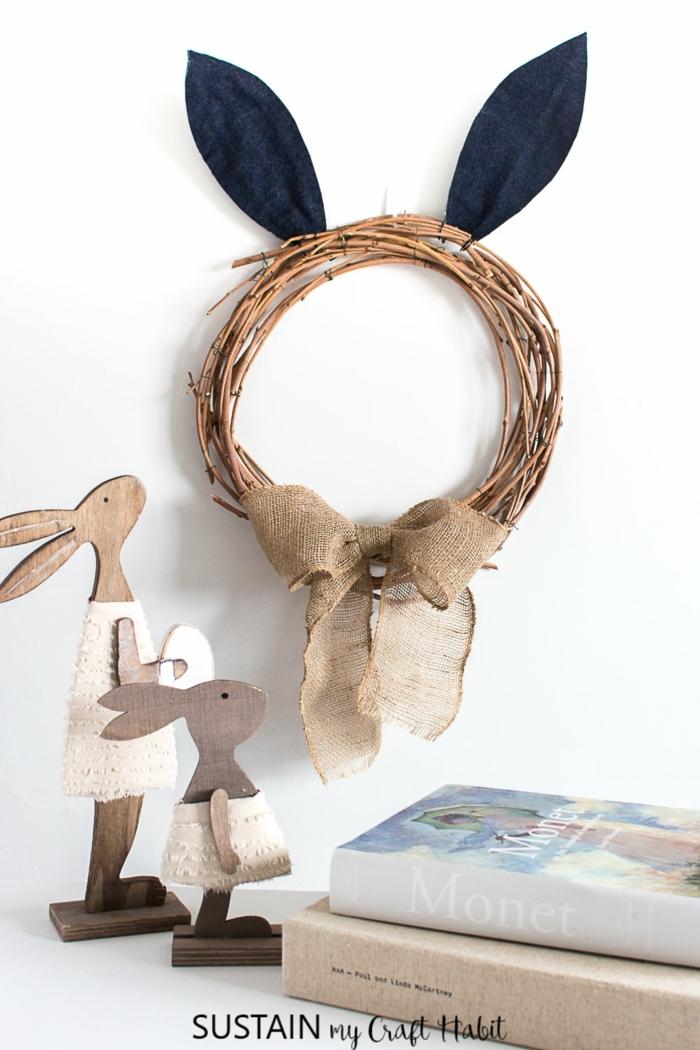 Osterkranz aus Zweigen mit schwarzen Ohren und brauner Schleife, zwei kleine und große Hasen aus Holz, Pinterest Osterdeko