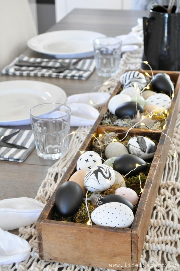 Tafelsufsatz von einem Holzkasten gefüllt mit Eier bemalt in verschiedenen Weisen, Osterdeko Holz, Servietten falten Ostern in Form von Osterhasenohren