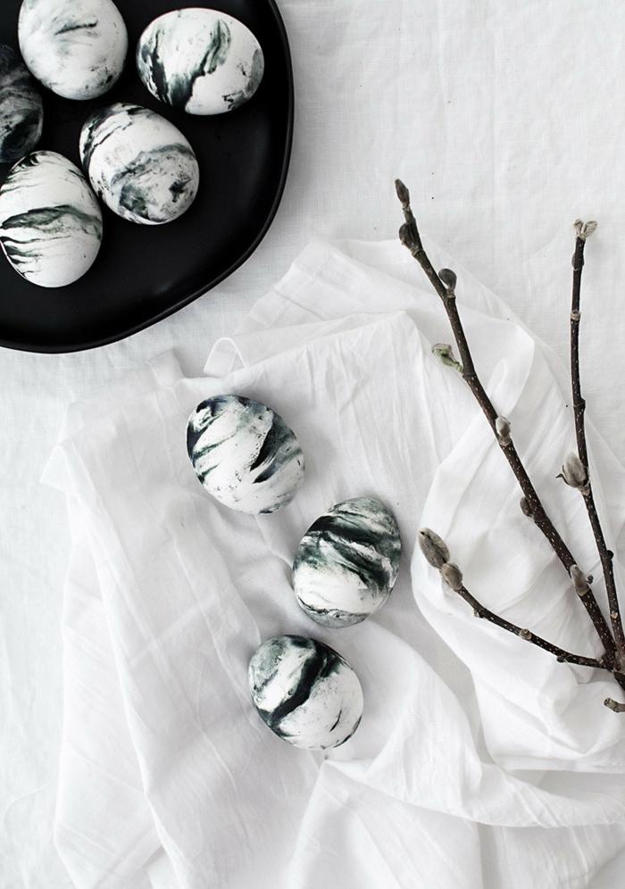 Ostereier bemalt in schwarz und weiß mit Marmoreffekt, minimalistische Osterdekoration, Eier in einem schwarzen Teller,