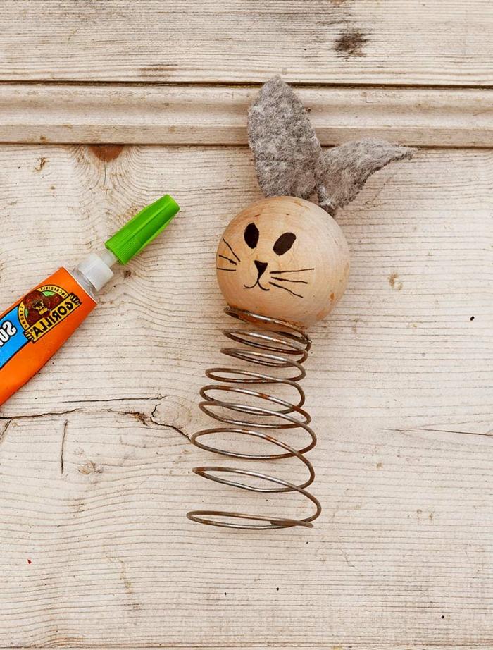 DIY Osterhase aus Holz und Feder, Kopf aus Holzkugel. Osterhasen basteln mit Kindern, graue Ohren, gemaltes Gesicht