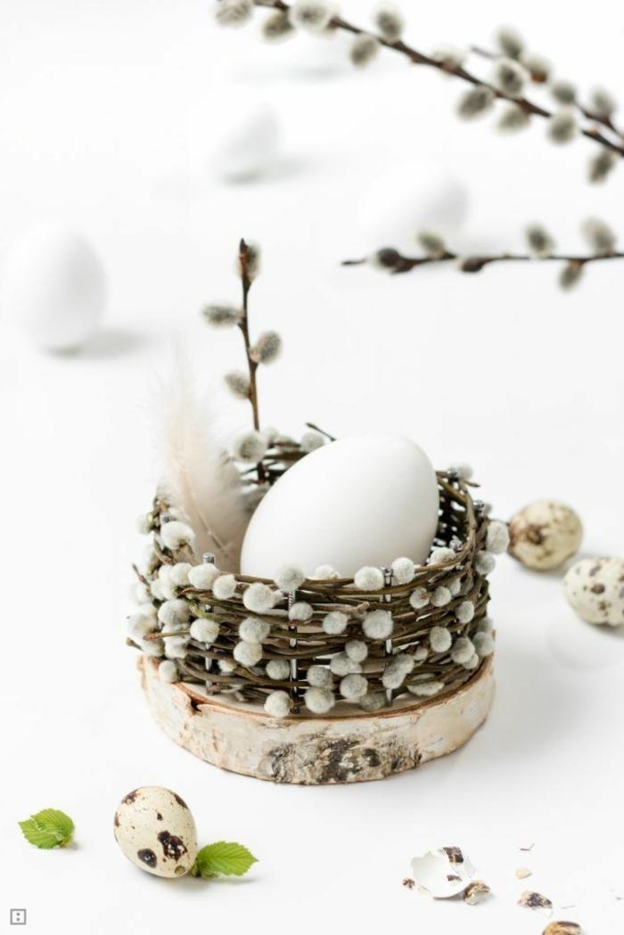 Osterdeko basteln aus Naturmaterialien, kleines Osterkörbchen aus Kätzchen Zweige auf einer Holzscheibe mit einem weißen Ei drin, Osterdeko selber machen