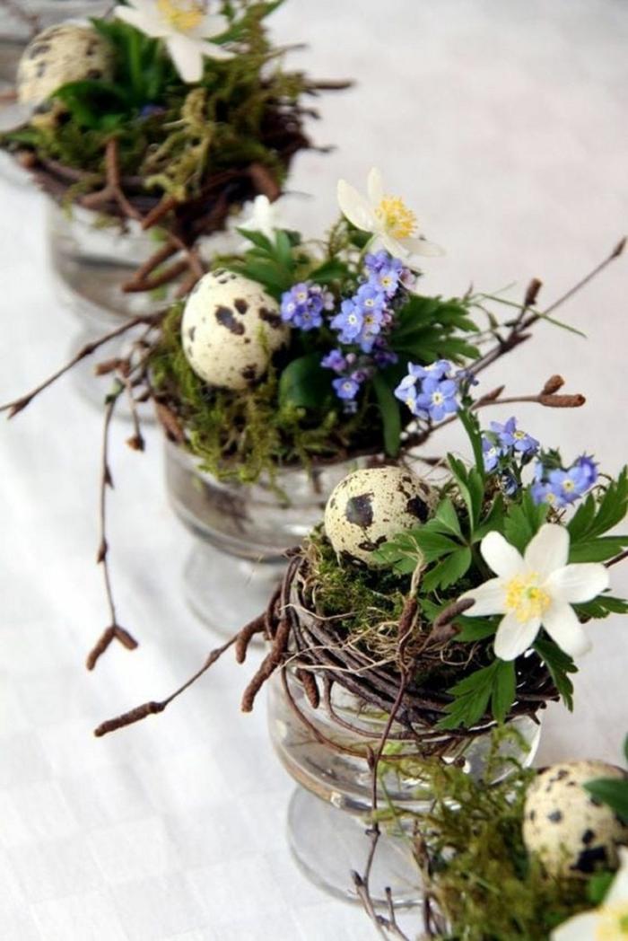 Osterdeko basteln aus Naturmaterialien für den Tisch, kleine Vasen mit kleinen Kränzen mit weißen und blauen Blumen und Eier,