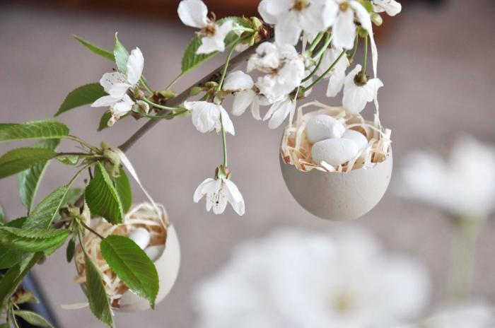 Upcyclen von Eierschalen, Schale mit künstlichem Heu und Ei aus Gips aufgehängt auf einem Zweig, Frühlingsdeko aus Naturmaterialien selber machen