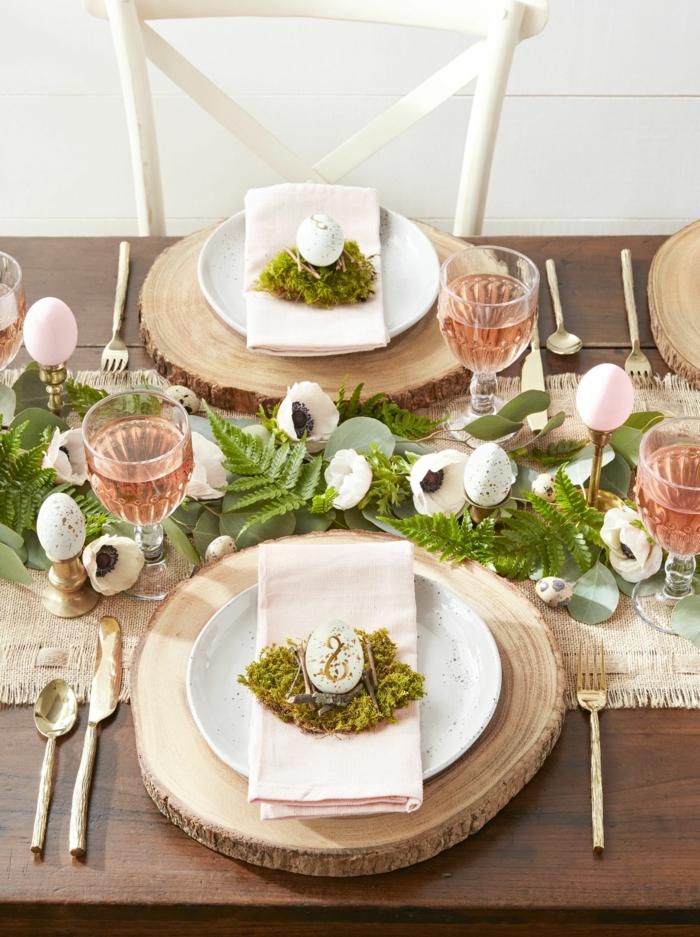 Tischdeko Frühling mit Naturmaterialien, Teller auf einem runden Holzbrett, Tafelaufsatz aus weißen Blumen und grünen Blättern