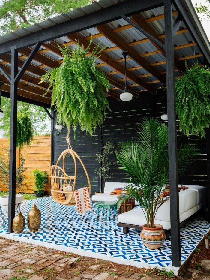 Garten eingerichtet mit Pergola in schwarz, geometrischer Teppich in blauen Tönen, viele grüne Pflanzen, hängende Schaukel,, gartendeko basteln aus naturmaterialien