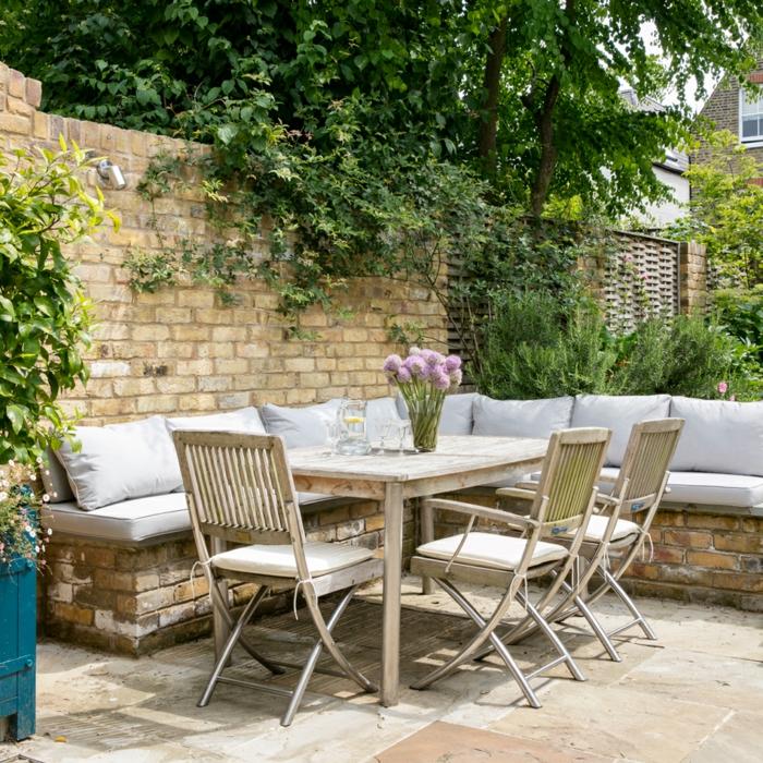 Deko Ideen mit Steinen im Garten, Ecksofa aus Ziegelsteinen, mit hellen Kissen, lila Blumen auf einem rechteckigen Tisch, Gartendeko Ideen,