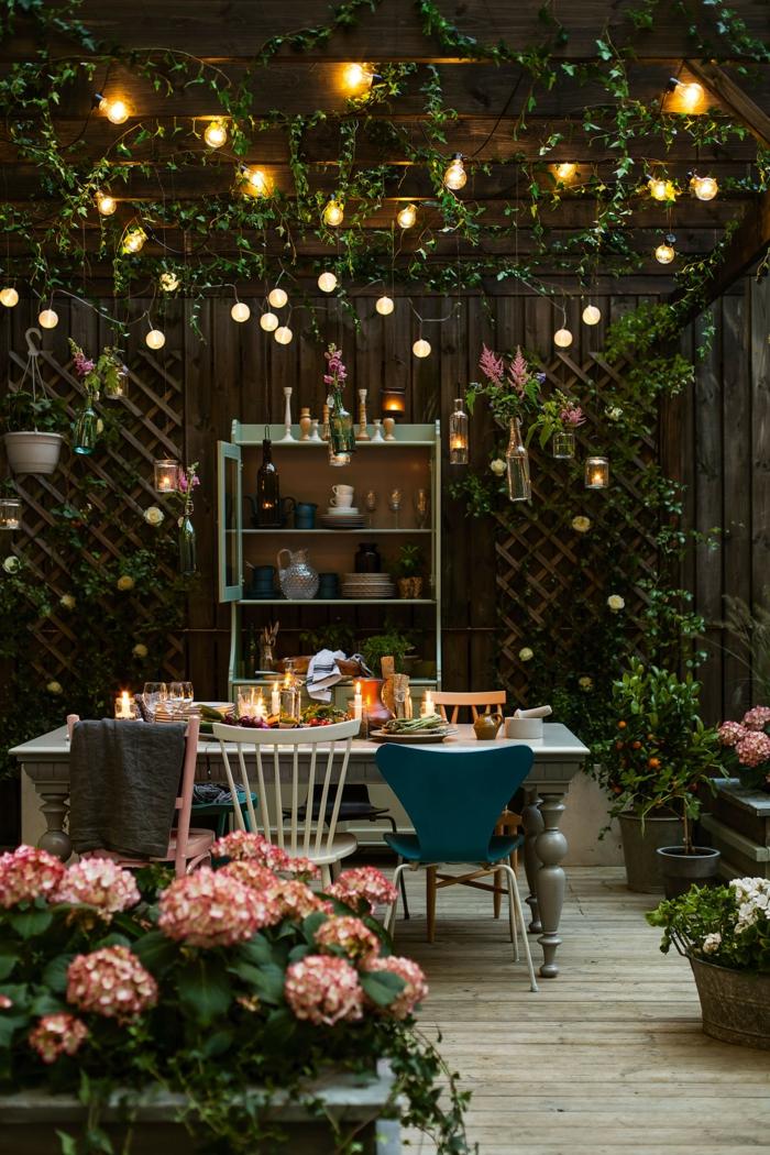 schöne beleuchteter Garten mit Lichterketten, pinke Blumen, stylische Dekoration, Gartengestaltung Ideen, Sichtschutz aus Holz