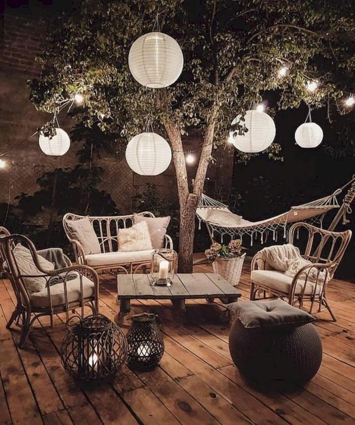 romantische Gestaltung im Garten mit großen hängenden Lamoen, Gartendeko aus Holz, Hängematte in weißer Farbe