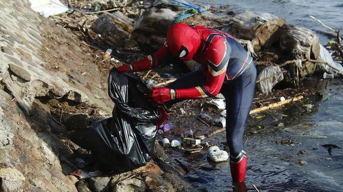 stdand der insel sulawesie, der einheimischer rudi hartono, der im kostüm von spiderman den müll an den strand von sulawesi aufräumt