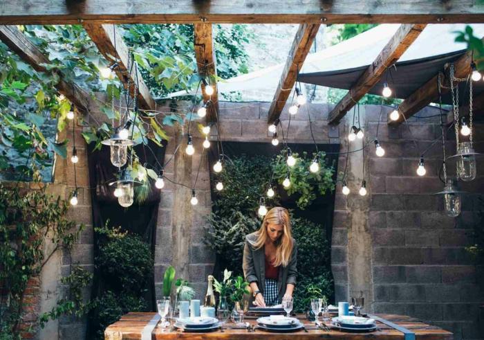Blonde Frau deckt Tisch in einem Garten im rustikalen Stil. hängende Lichterketten, Gartendeko Ideen, grüne Pflanzen Dekoration