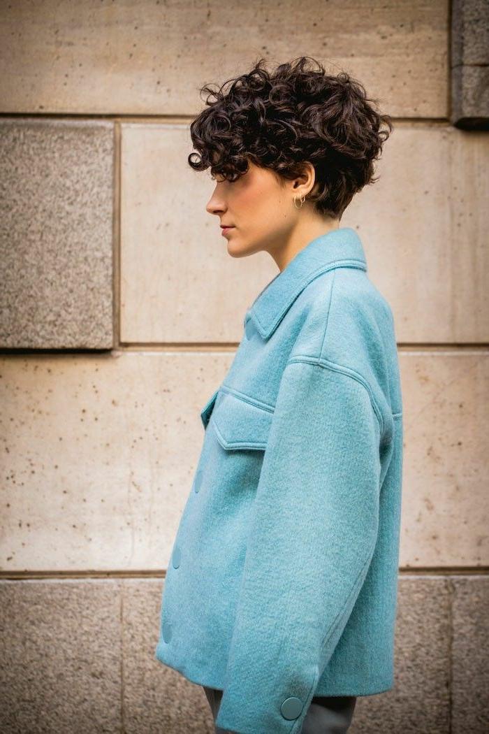 stylisch angezogene Frau in blauer weiter Jacke, lockige Kurzhaarfrisuren, braune bis sehr dunkle Haare, Street Style Fotografie