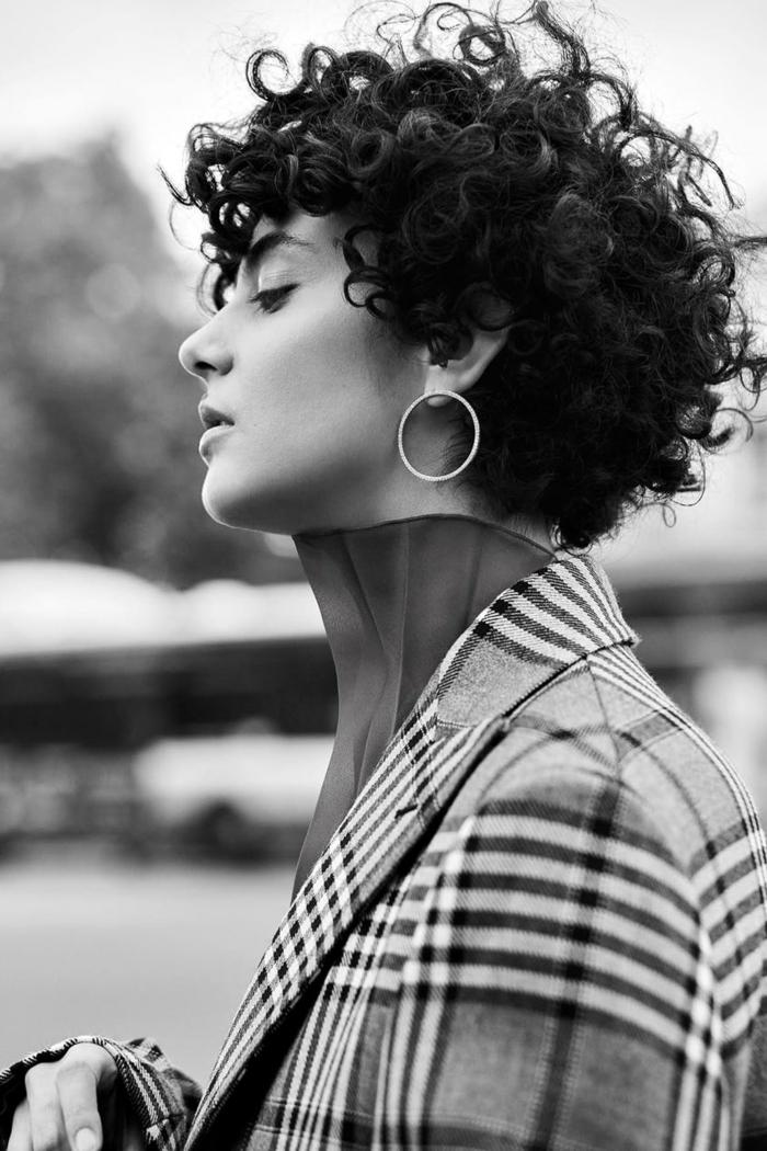 Schwarz weiße Fotografie von einer eleganten Frau, kurze dunkle Haare, moderne Kurzhaarfrisuren, karierter Mantel, kleine Kreolen