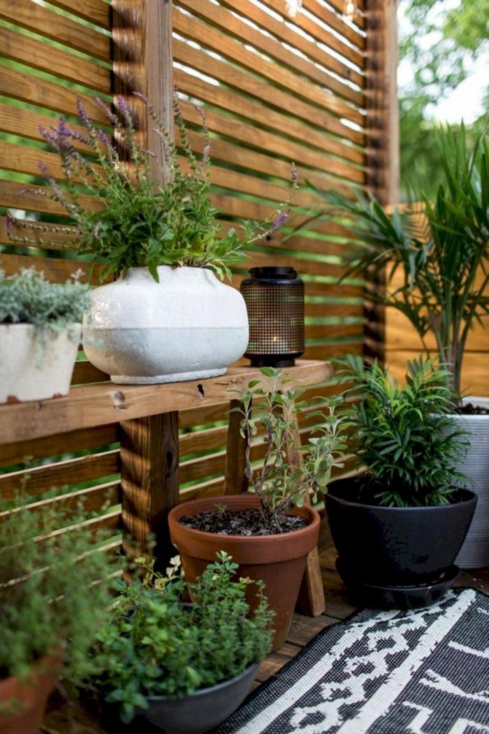 Mit Pflanzen dekorierter Garten, Sichtschutz aus Holz, Garten Ideen selber machen, schwarz weißer Teppich