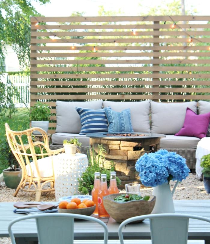 Sichschutz aus Holzbretter im Garten, graues Sofa mit bunten Kissen, Ideen Gartengestaltung, blauer Esstisch, blaue Blumen in Vase