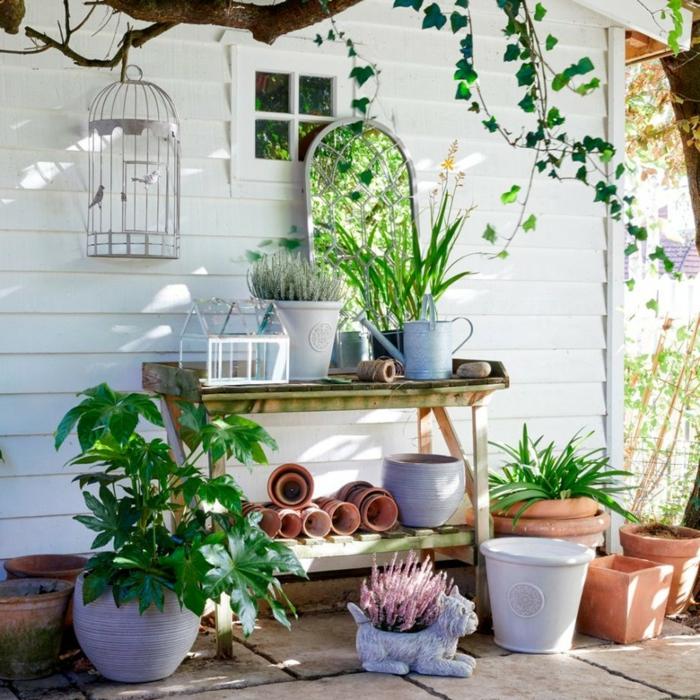 Spiegel in einem Garten, viele Pflanzentöpfe und Gartenzubehör, weiße Wand, Ideen Gartengestaltung modern