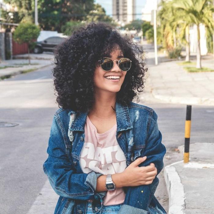 lächelnde junge Frau, gekleidet in Jeansjacke und pinkes T-Shirt, Naturlocken kurz schneiden, runde Sonnenbrillen