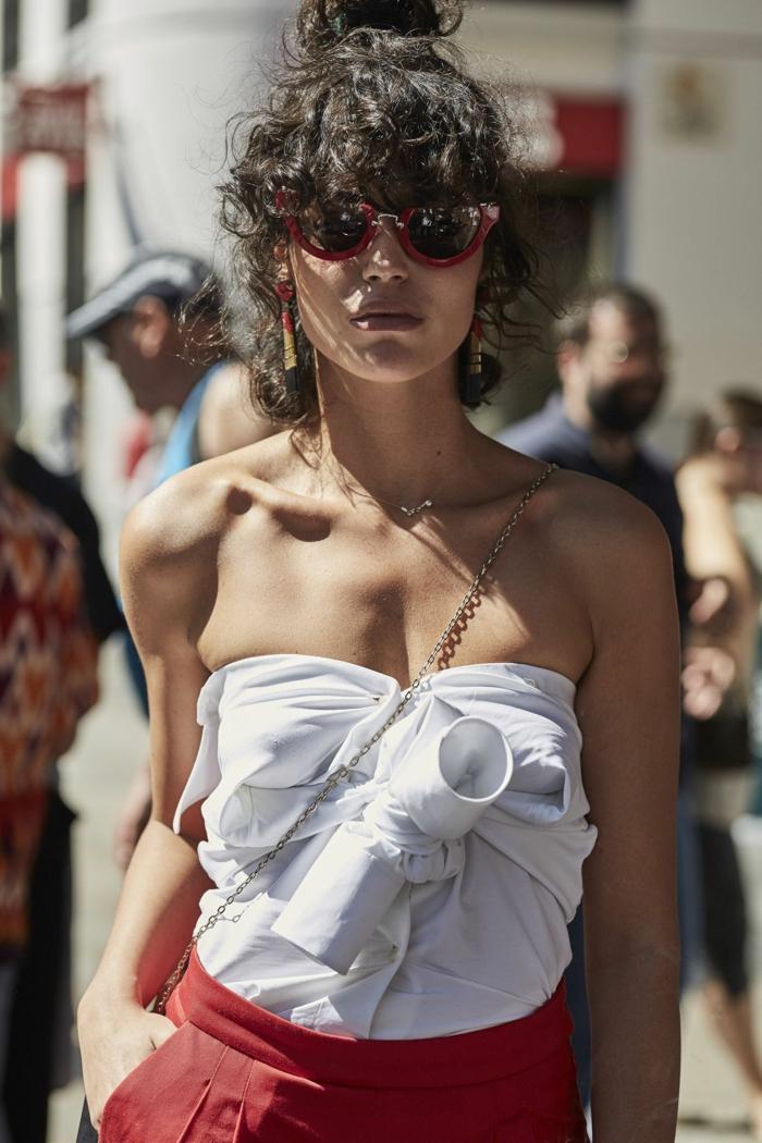 modern angezogene Frau in roten Hosen und weißes trägerloses Top, Kurzhaarfrisuren Locken, Street Style Fotografie
