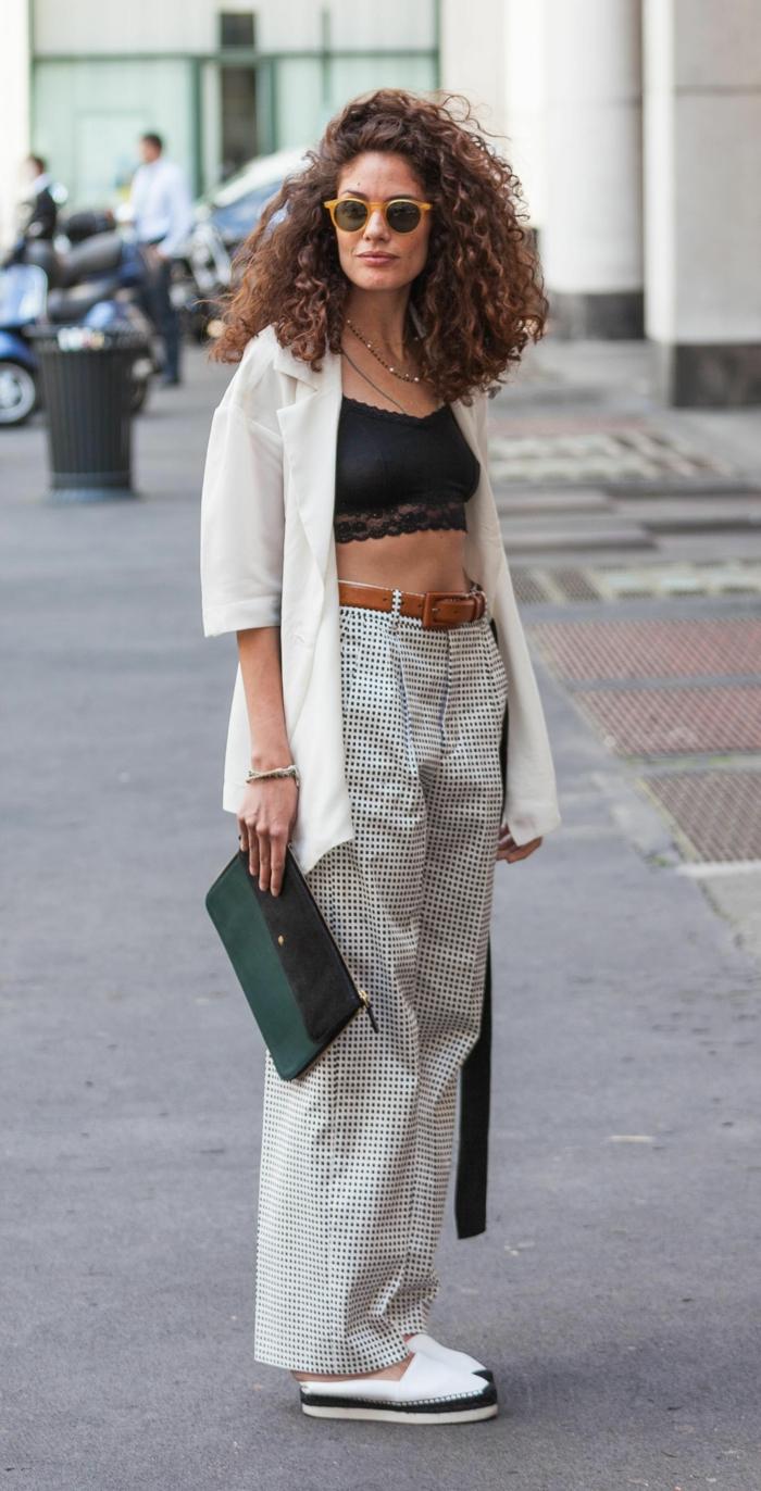 Street Style Inspiration Looks, lockige Kurzhaarfrisuren, Frau im schwarzem Crop Top und weißem Cardigan, weite karierte Hosen, weiße Schuhe und grün-schwarze Clutch,