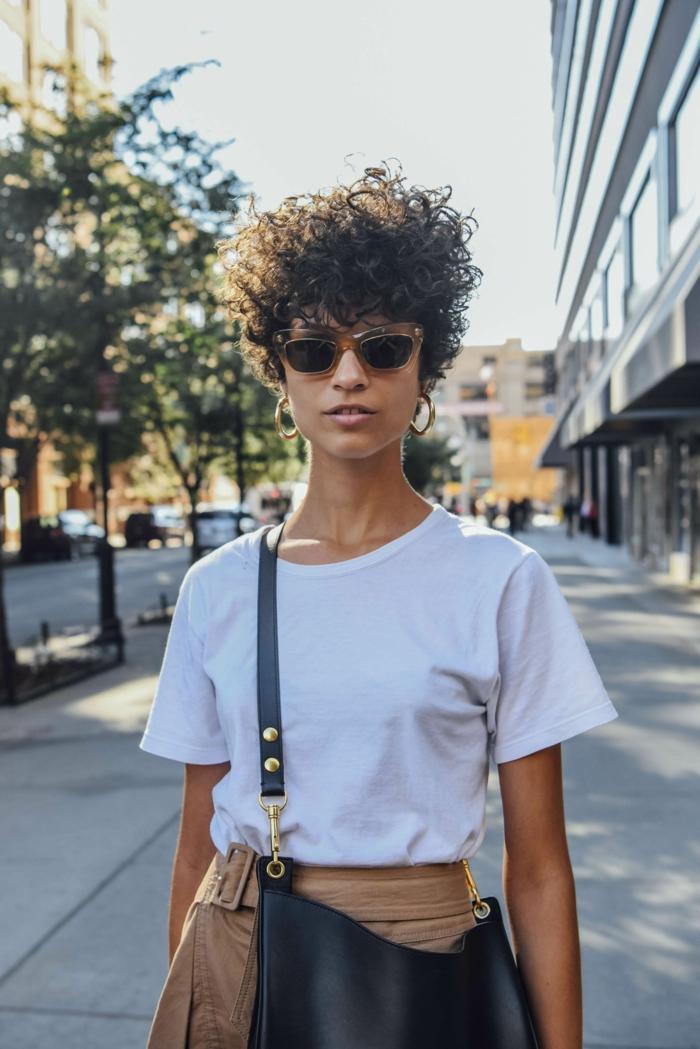 New York Street Style Inspiration, lockige Kurzhaarfrisuren, lässig gekleidete Frau, hellbraune Hosen mit Gürtel und weißes T-Shirt, schwarze Umhängetasche