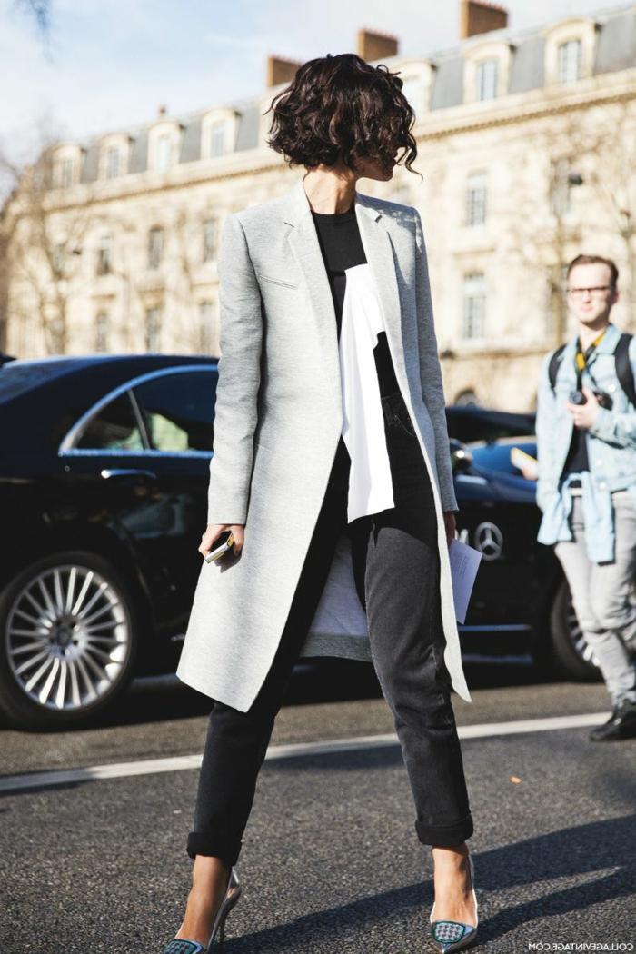 Frisuren mit Locken, elegante Dame im langen grauen Mantel, schwarze Jeans und High Heels, schwarzes Auto im Hintergrund