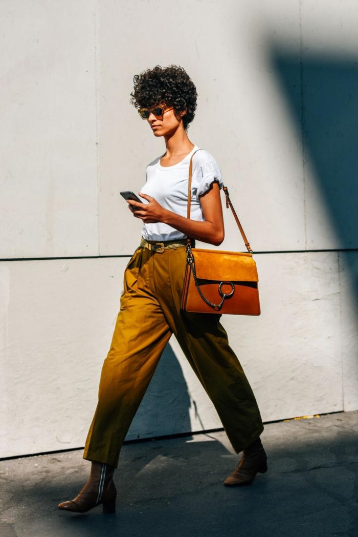 Styling Inspiration, Haarschnitt Locken, modern gekleidete junge Frau in weiten ockerfarbenen Hosen und weißes T-Shirt, braune Ledertasche,