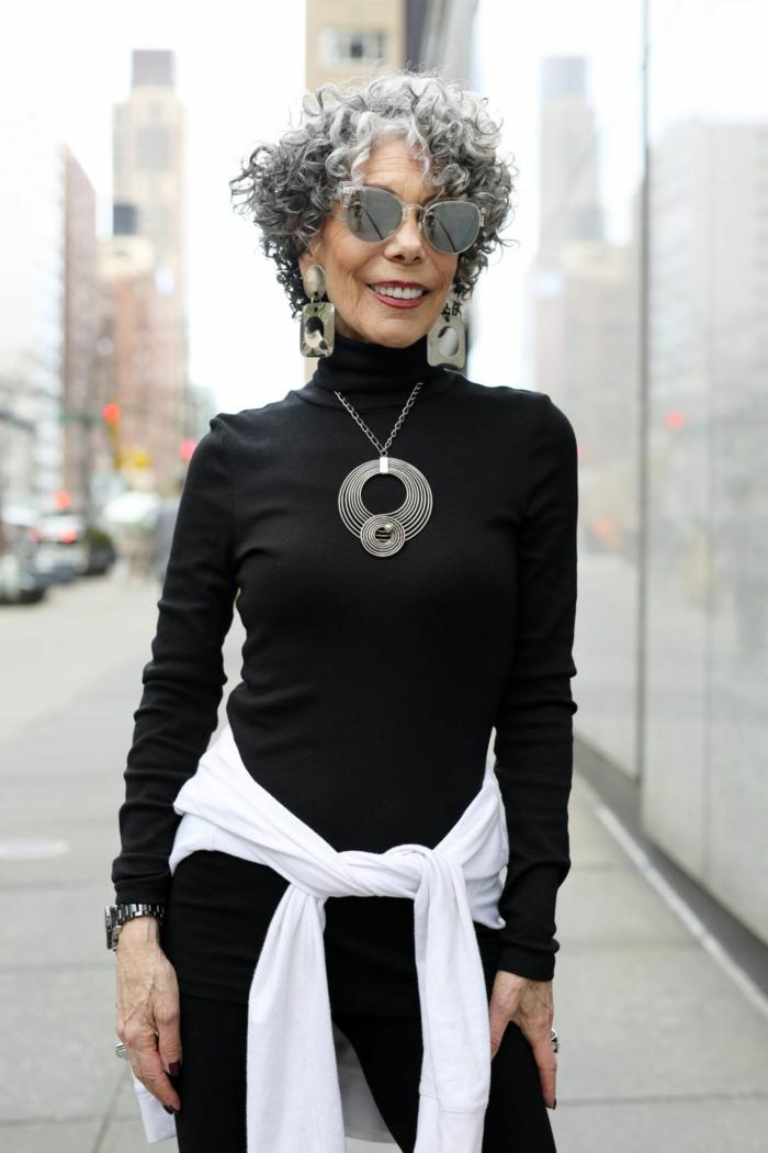 Elegante Dame mit grauen lockigen Haaren, schwarzes Outfit mit Rollkragenpullover, schicke Kurzhaarfrisuren, eindrucksvolle Halskette
