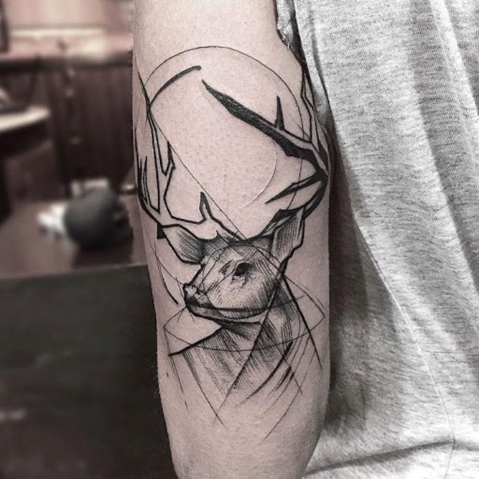 symbol für stärke, hirsch mit geometrischen motiven, oberarm tattoo in schwarz und grau