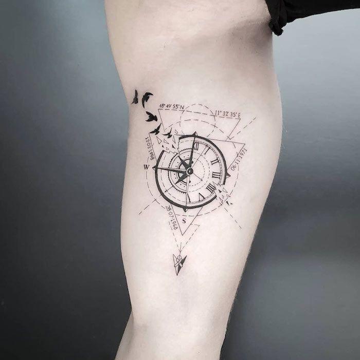 tattoo arm mann, kompass in kombiantion mit koordinaten und fliegenden vögeln