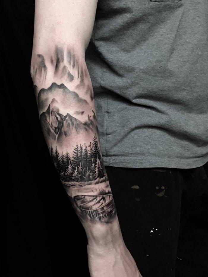 tattoo unterarm mann, schwarz graue tätowierung mit landschaft als motiv, gebirge, wald