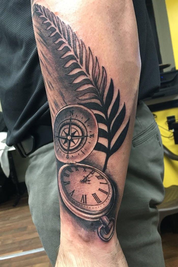 tattoos männer arm, taschenuhr in kombination mit kompass und großem feder