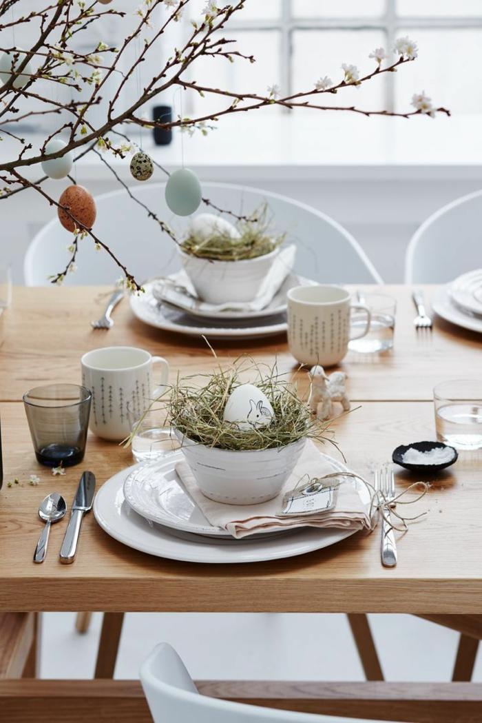 Tischdeko Frühling mit Naturmaterialien, Baum mit aufgehängten Eier, weiße Schale mit Heu und weißem Ei