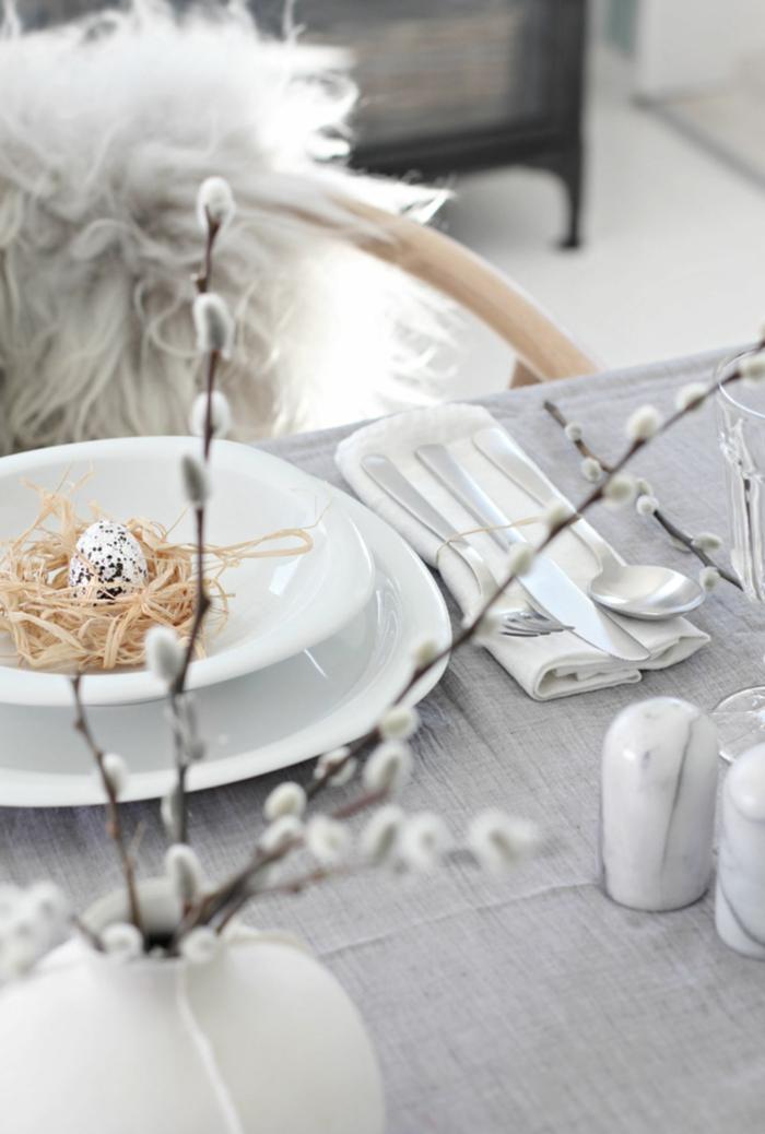 minimalistsche tischdeko zu ostern, pinterest osterdeko, graue Tischdeke, Vase mit Kätzchen Blume, Schale mit künstlichem Heu und kleinem Ei