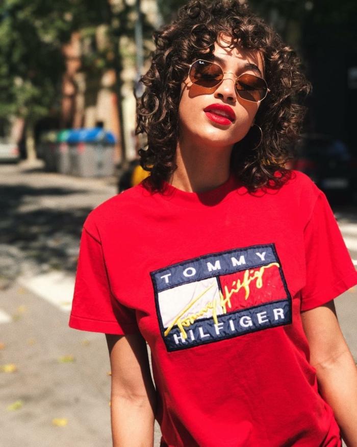 Naturlocken kurz schneiden, Frau im roten Tommy Hilfiger weites T-Shirt, Street Style Fotografie, Hexagon Sonnenbrillen