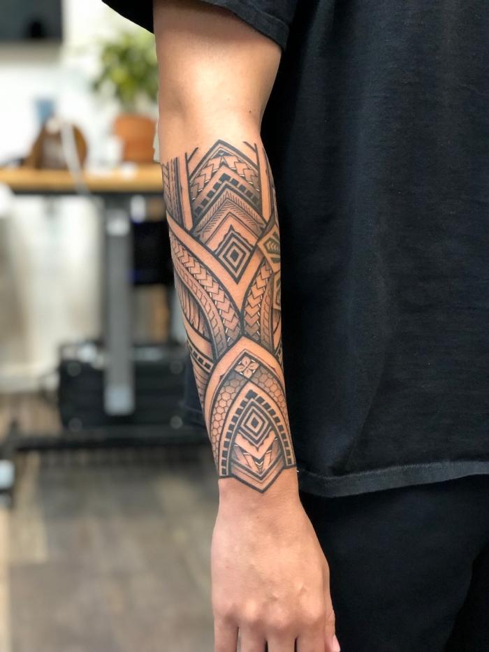 tribal tattoo am unterarm, tätowierung in schwarz grau am unterarm, geometrische motive