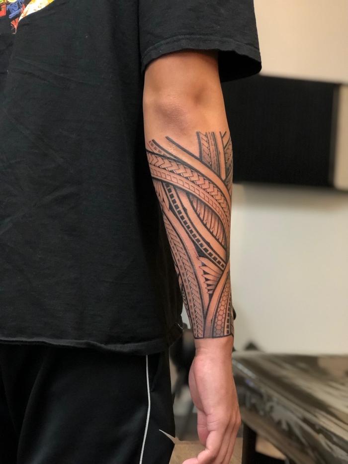 tribal tattoo designs für herren, schwarz graue tätowierung am unterarm, mann
