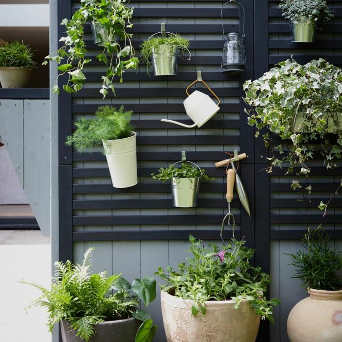 Pflanze und eine Gießkanne aufgehängt auf eine schwarze Wand, Gartendeko aus Holz, hängende Pflanzer
