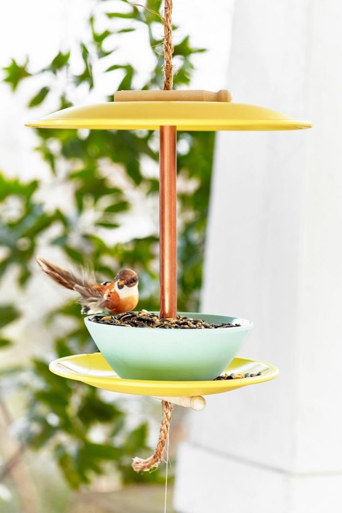 Garten Ideen selber machen, DIY Vogelhaus aus alten Tellern in gelb, kleiner Vogel isst Futter aus einer Schale,