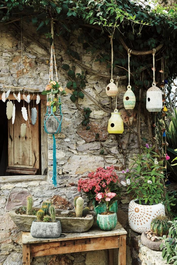 vier kleine selbstgemachte Vogelhäuser, viele Blumen und Kakteen, Wand eines Hauses aus Stein, Gartendeko selbstgemacht