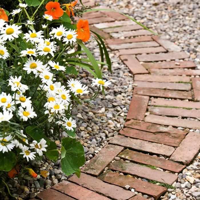 Weg in einem Garten aus dunkelrote Zigeln, Boden mit Zierkies, Gänseblümchen und orange Blumen, Garten Ideen selber machen