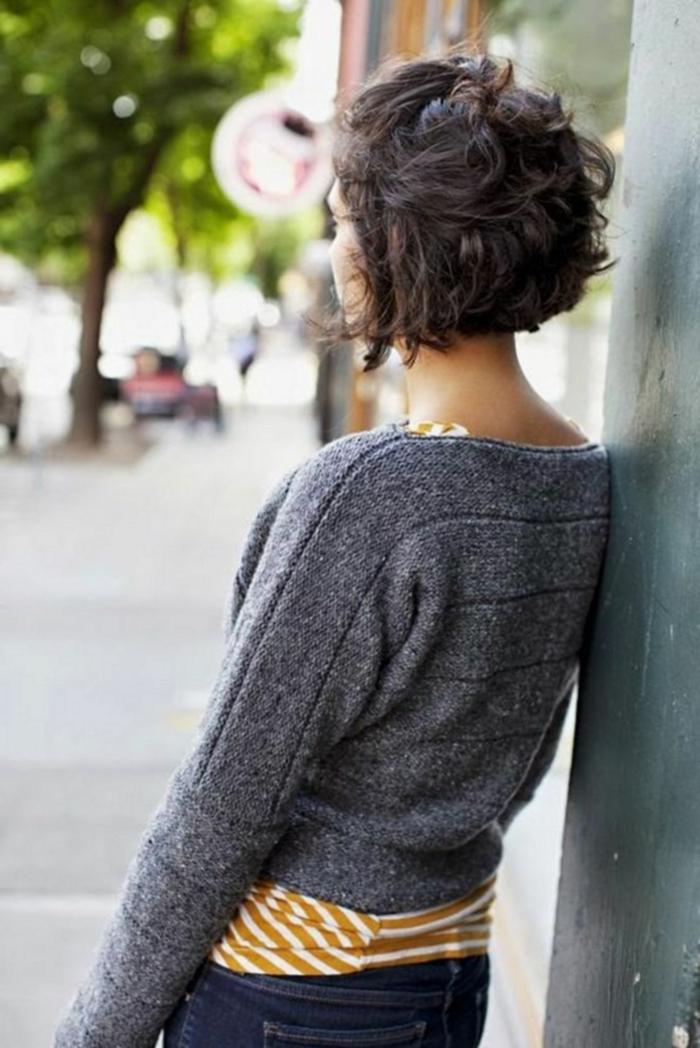 Frau im grauen Pullover und dunkle Jeans, Foto auf der Straße, Halb hoch Frisur, lockige Kurzhaarfrisuren, braune Haare