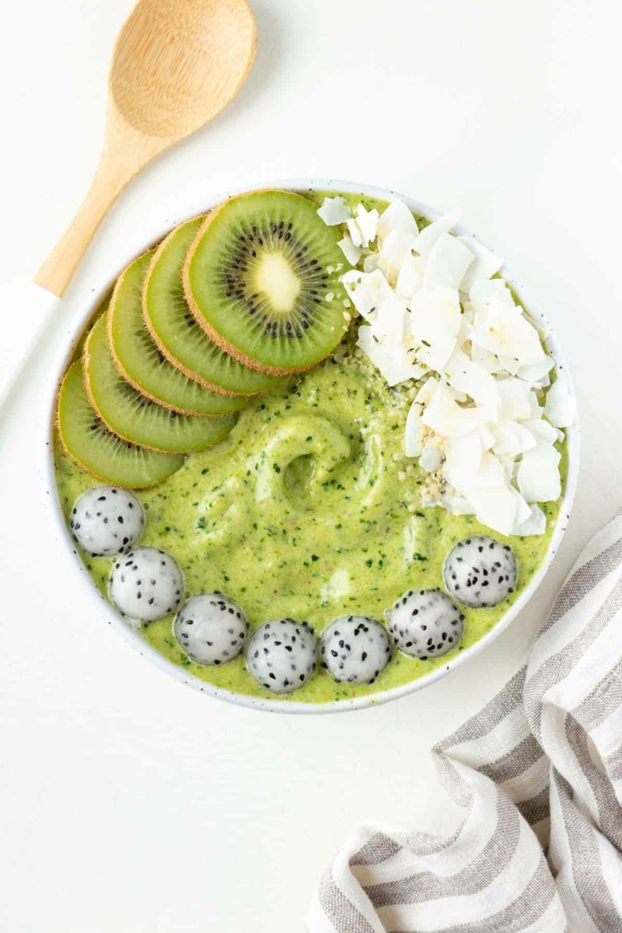 grüne Smoothiebowl Rezept mit Bananen Grünkohl und Ananas, dekoriert mit Kokosnussflocken und Kiwi, low carb Rezepte vegan, großer Löffel aus Holz